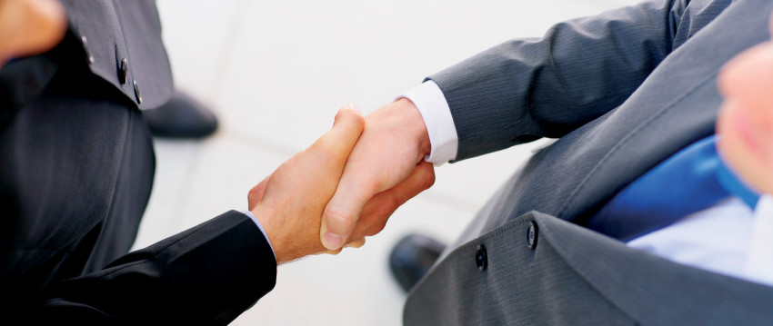 Businesspeople shaking hands, finishing up a meeting.