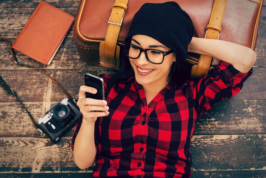 Top view of beautiful young woman in headwear lying on the floor holding mobile phone and smiling